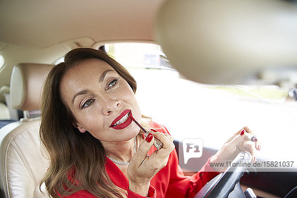 Portrait of mature woman applying lipp gloss in car