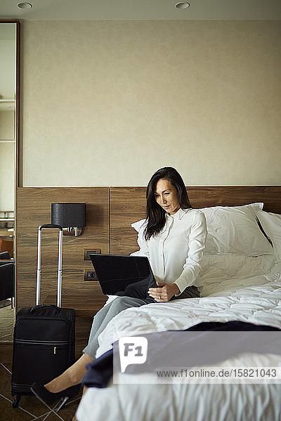 Geschäftsfrau sitzt mit Laptop im Hotelzimmer auf dem Bett