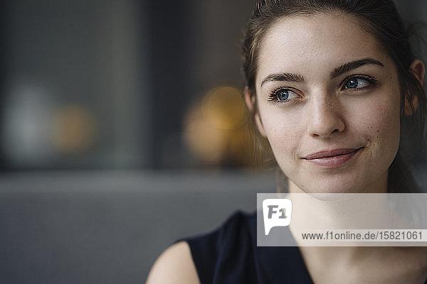 Porträt einer lächelnden jungen Frau  die in die Ferne schaut