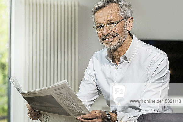 Portait of smiling senior man with grey hair in modern design living room reading newspaper