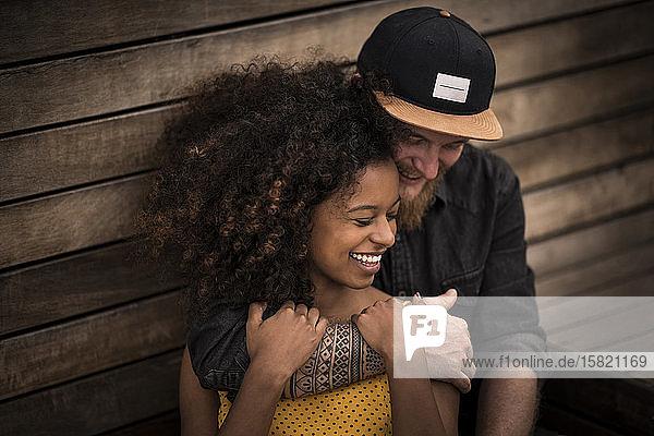 Glückliches Paar umarmt sich an Holzwand