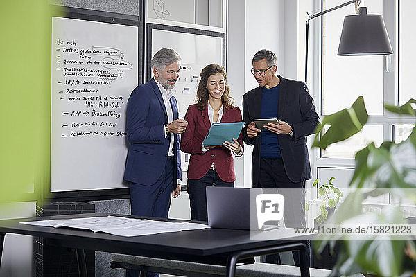 Zwei Geschäftsmänner und eine Geschäftsfrau arbeiten gemeinsam an einem Projekt im Amt