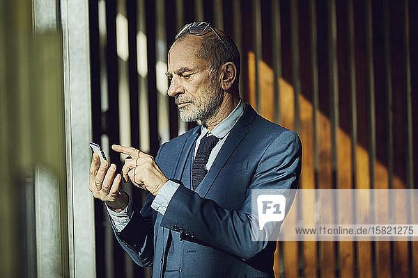 Leitender Geschäftsmann steht in seinem nachhaltigen Büro und benutzt ein Smartphone