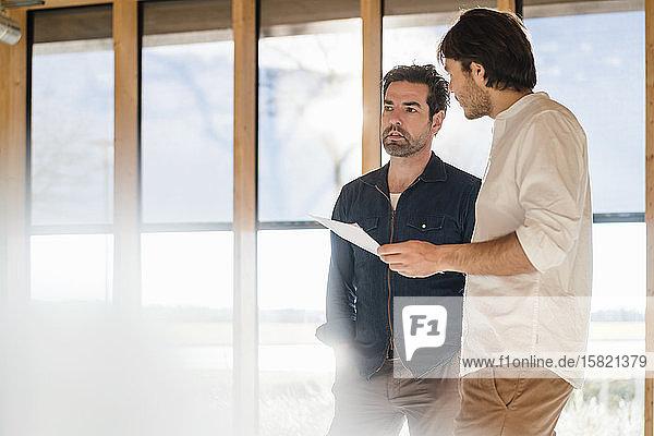 Zwei Geschäftsleute mit Dokumenten im hölzernen Großraumbüro im Gespräch