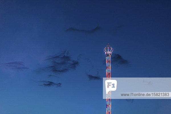 Deutschland  Bayern  München  Niederwinkelansicht der Kettenschaukel des Bayern-Turms  die in der Dämmerung gegen den Himmel leuchtet
