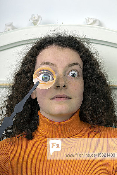 Portrait of starring young woman with paper mask