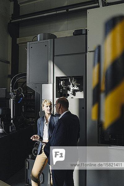 Geschäftsmann und Geschäftsfrau mit Tablettengespräch in einer Fabrik