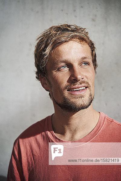 Porträt eines Mannes in rotem T-Shirt mit Blick nach oben