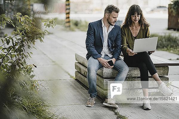 Geschäftsmann und gelegentliche Geschäftsfrau mit Laptop im Freien