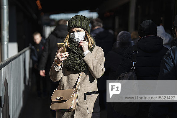 Woman with face mask standing at bus stop  using smartphone