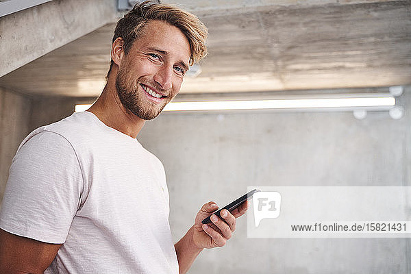 Portrait of attactive young man wearing white t-shirt holding smartphone