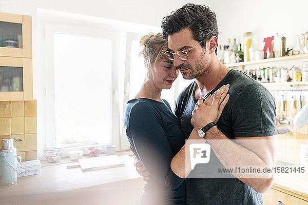 Affectionate couple dancing in kitchen at home