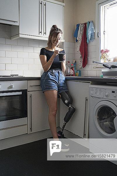 Junge Frau mit Beinprothese trinkt zu Hause in der Küche Kaffee
