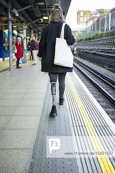 Rückansicht einer jungen Frau mit Beinprothese beim Gehen am Bahnsteig