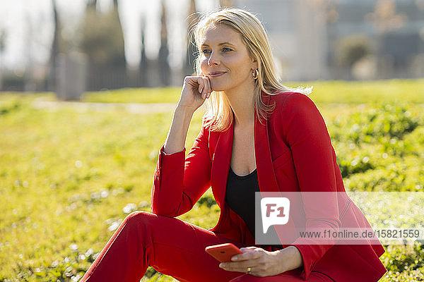 Blonde Geschäftsfrau in rotem Anzug mit Smartphone und auf einer Wiese sitzend