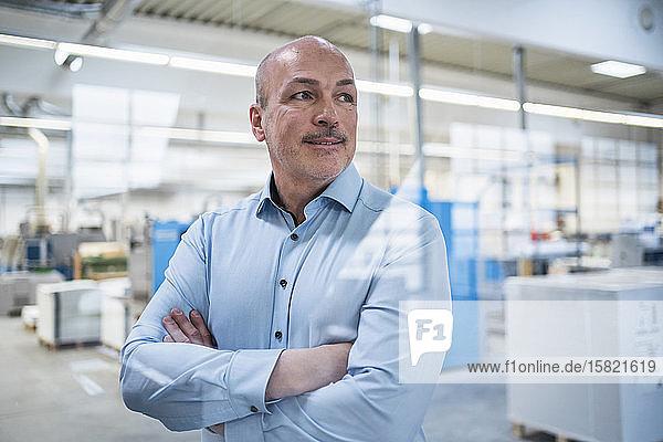 Porträt eines selbstbewussten Geschäftsmannes in einer Fabrik