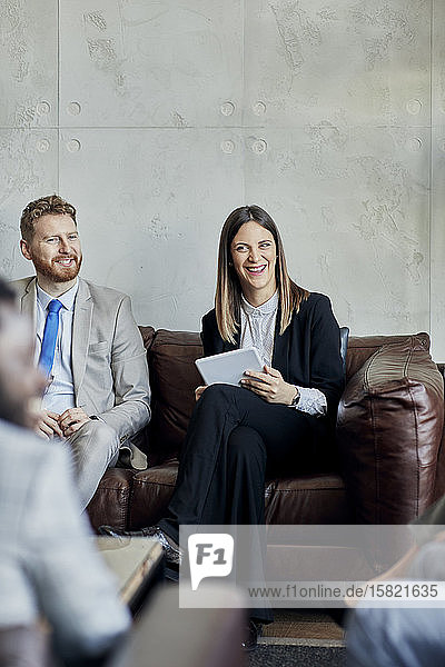 Happy businessman and businesswoman sitting on couch in hotel lobby during a meeting