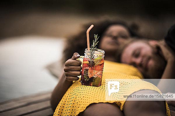 Junge Frau liegt mit ihrem Freund am Boden und hält frisches Eisteegetränk in der Hand