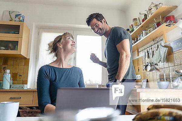 Glückliches Paar in der Küche mit Laptop