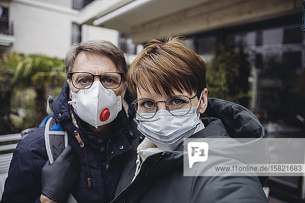 Couple  wearing protective masks  taking a sefie