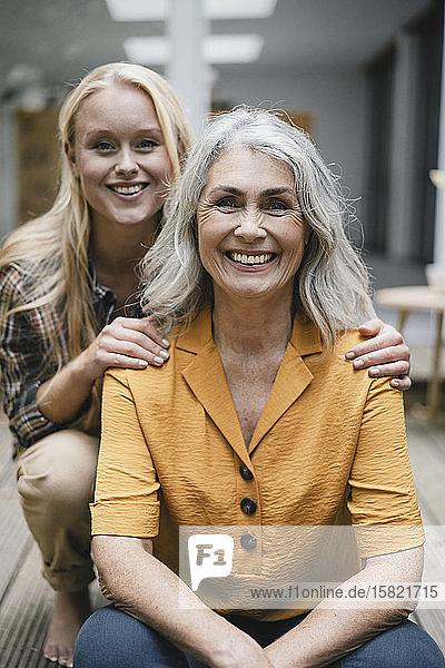 Porträt einer glücklichen Mutter und einer erwachsenen Tochter auf der Terrasse
