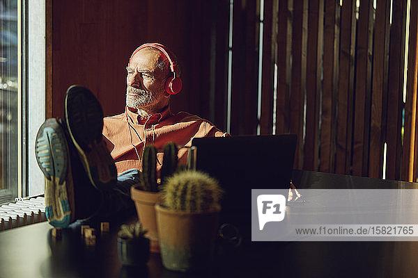 Entspannter Geschäftsmann macht eine Pause  hört Musik mit Kopfhörern in seinem nachhaltigen Büro