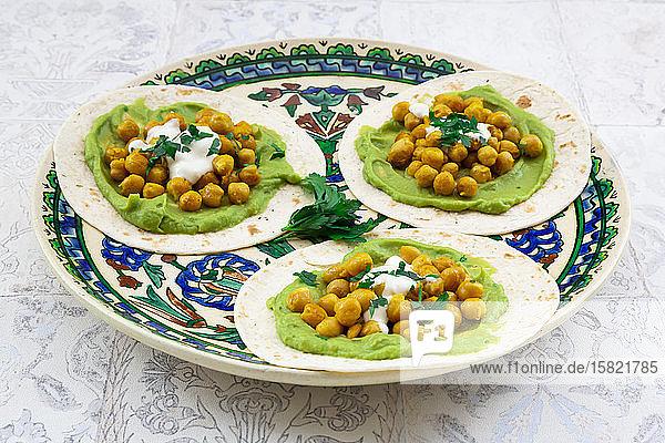 Fladenbrotteller mit Avocadopüree  Kurkuma-Kichererbsen  Joghurt und Petersilie