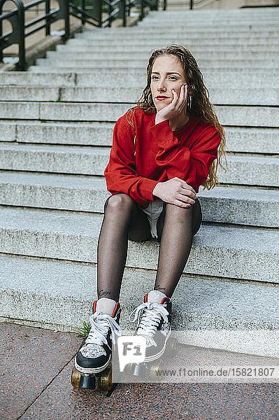 Junge Frau mit Rollschuhen auf einer Treppe sitzend