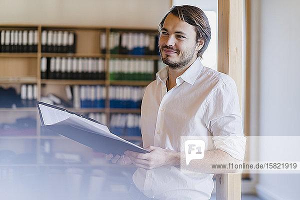 Geschäftsmann mit Ordner im hölzernen Großraumbüro