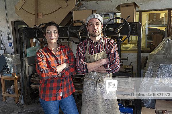 Porträt einer selbstbewussten Handwerkerin und eines Handwerkers in ihrer Werkstatt