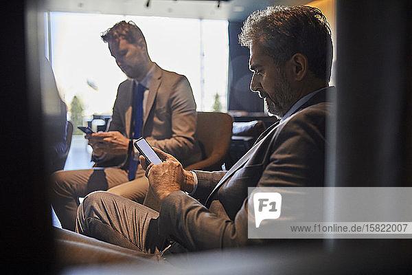 Zwei Geschäftsleute benutzen Smartphones in der Hotellobby