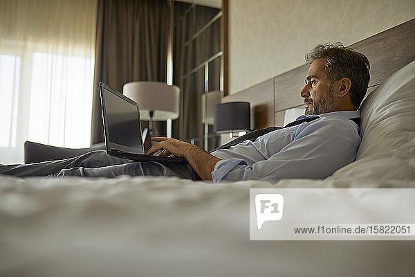 Geschäftsmann im Hotelzimmer auf dem Bett liegend mit Laptop