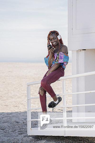 Lächelndes Teenager-Mädchen mit Kopfhörern und Smartphone am Strand