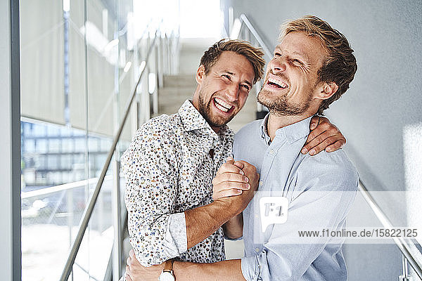 Portrait of two happy young businessmen shaking hands