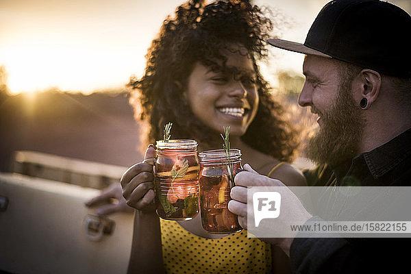 Glückliches Paar klirrt bei Sonnenuntergang mit frischen Eisteegetränken im Freien