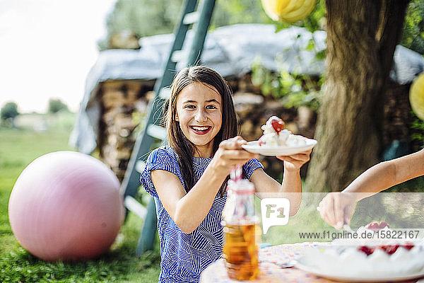 Porträt eines glücklichen Mädchens  das auf einer Geburtstagsfeier im Freien ein Stück Kuchen erhält Porträt eines glücklichen Mädchens, das auf einer Geburtstagsfeier im Freien ein Stück Kuchen erhält