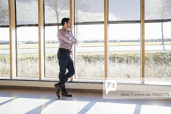 Geschäftsmann schaut im Großraumbüro aus dem Fenster