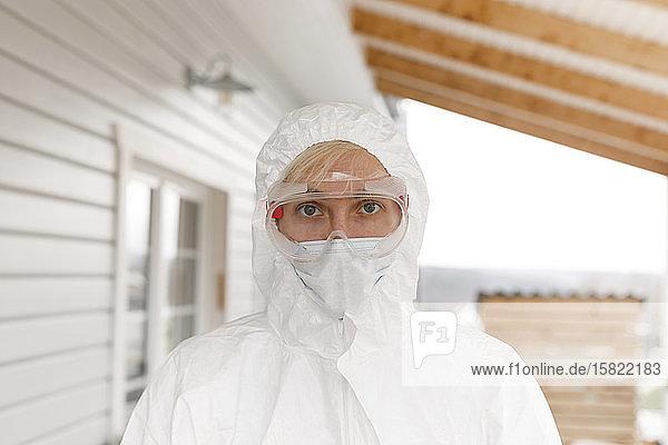 Mann in Schutzkleidung  steht vor dem Haus