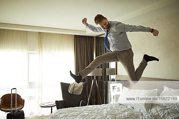 Aufgeregter Geschäftsmann springt im Hotelzimmer aufs Bett