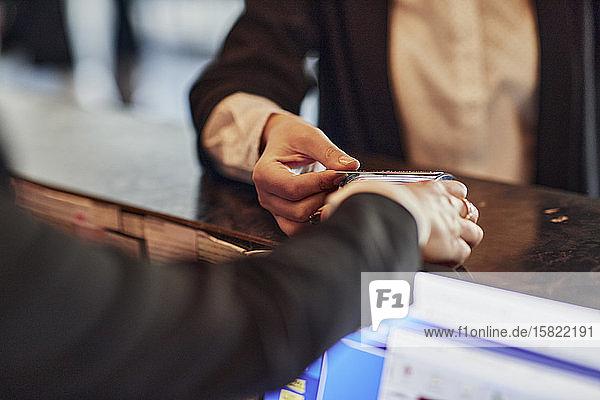 Nahaufnahme einer Frau  die an der Rezeption kontaktlos mit Kreditkarte bezahlt