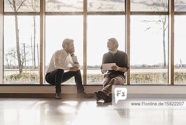 Zwei Geschäftsleute mit Tablett am Fenster im Großraumbüro im Gespräch