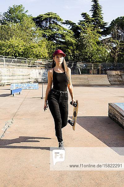 Junge Frau mit Skateboard und Smartphone in einem Skatepark