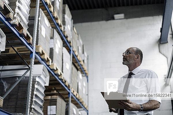 Mann mit Zwischenablage im Fabriklager