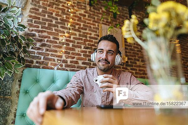 Lächelnder Mann in einem Café  der mit Kopfhörern Musik hört