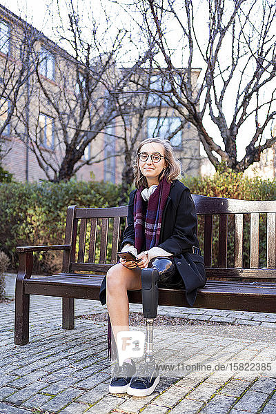 Porträt einer selbstbewussten jungen Frau mit Beinprothese  die auf einer Bank in der Stadt sitzt Porträt einer selbstbewussten jungen Frau mit Beinprothese, die auf einer Bank in der Stadt sitzt