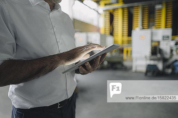Nahaufnahme eines Geschäftsmannes mit Tablette in einer Fabrik