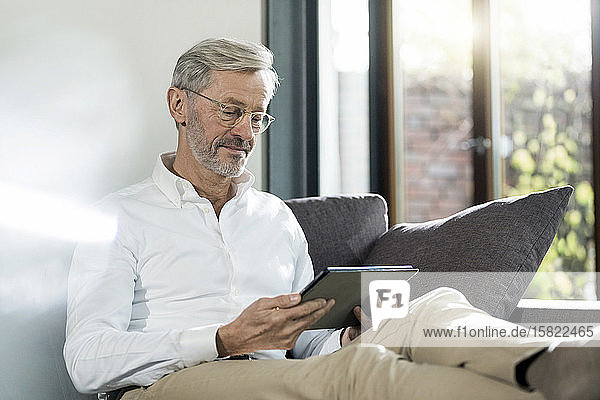 Senior man with grey hair in modern design living room sitting on couch using tablet