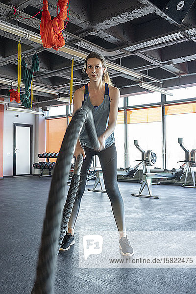 Young woman exercising with battle ropes at gym