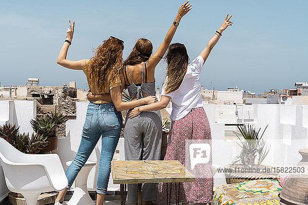 Rückansicht von drei jungen Frauen  die auf der Dachterrasse stehen und Siegeszeichen zeigen  Essaouira  Marokko
