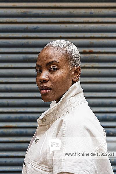 Porträt einer selbstbewussten Frau an einem Rollladen